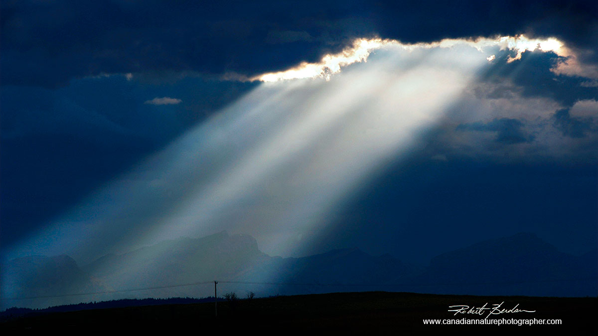 light rays breaking through the clouds in front of the Rocky Mountains Robert Berdan ©