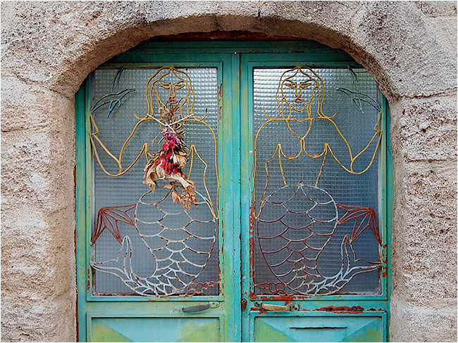 new window in an old Rhodes building. Mermaid motif with flowers. by John Laprairie ©