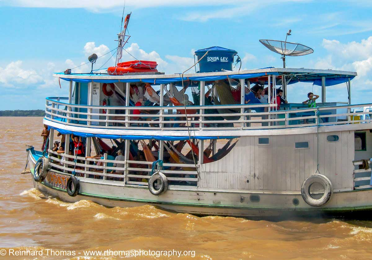 Typical Amazon river boat with hammocks slung from one side to the other by Reinhard Thomas ©