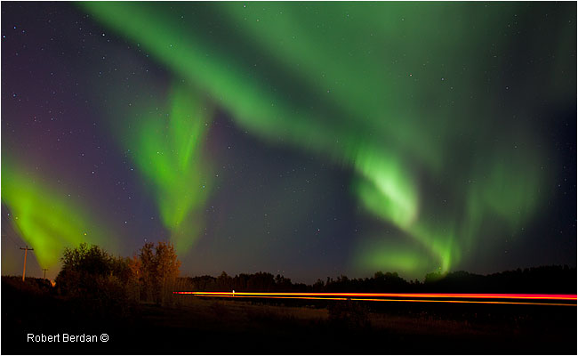 Car lights on road in High Level Alberta with Aurora overhead by Robert Berdan ©