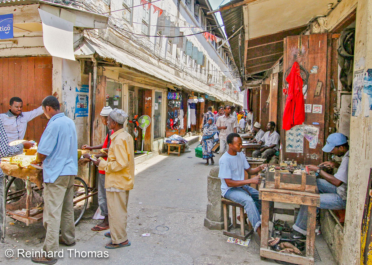 narrow street in Stone Town lined with vendors by Reinhard Thomas ©