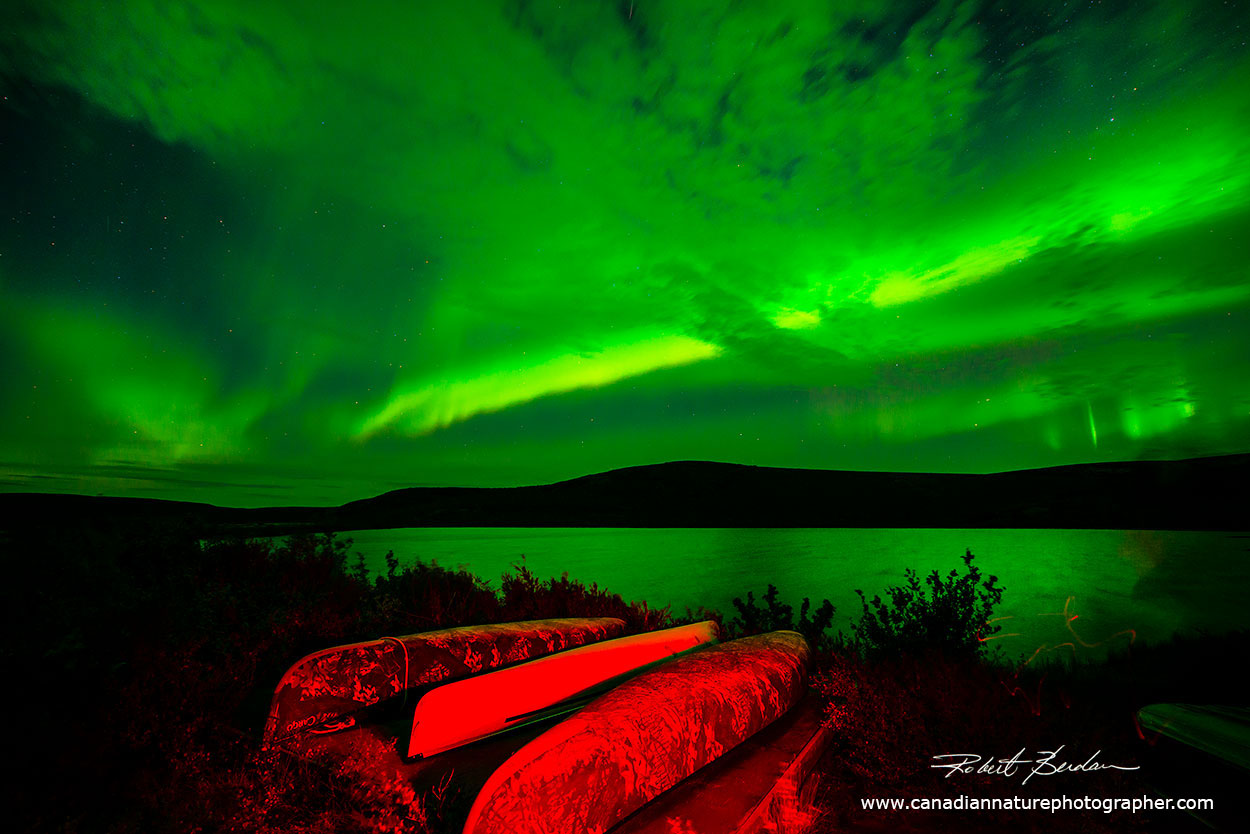 I used a red light to light-paint the canoes with the Aurora in the background by Robert Berdan ©