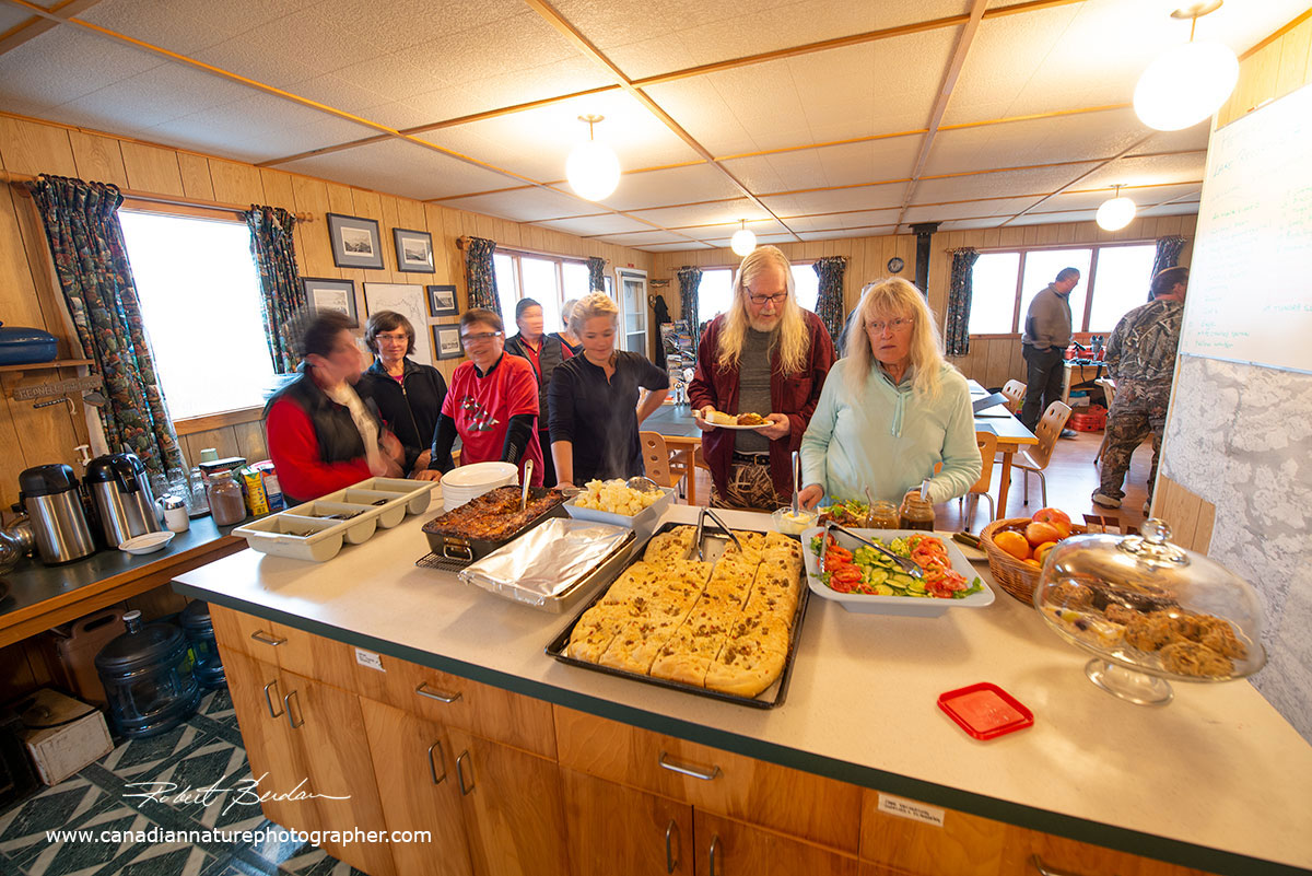 Guests line up for food at Point Lake Lodge by Robert Berdan ©
