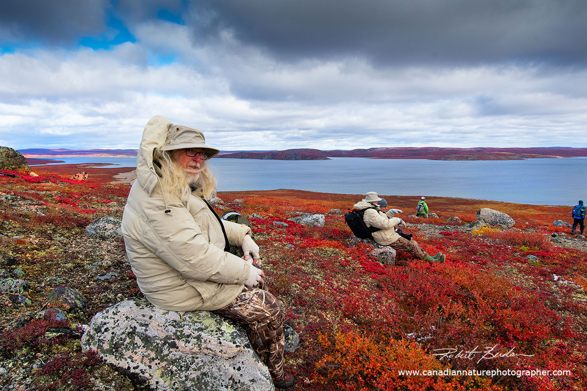 Elston Hill rests on a rock and surveys Point Lake, his wife Jackline is resting on the second rock by Robert Berdan ©