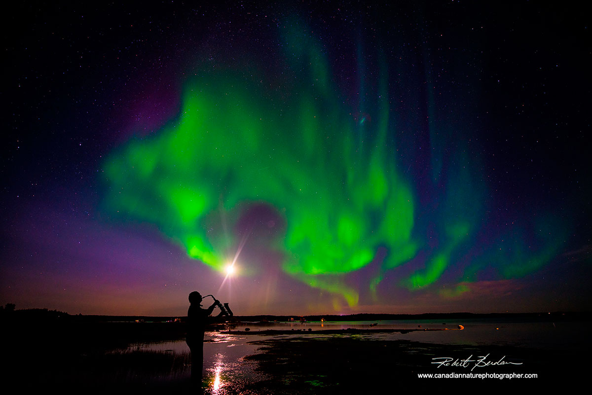 Saxophne player in front of Aurora Borealis Yellowknife, NT