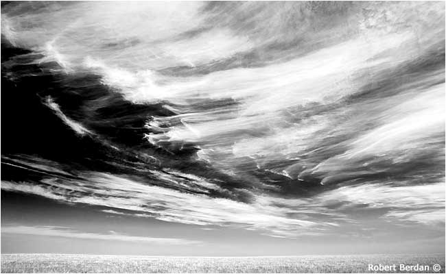 Cirrus clouds over Alberta prairie in black and white by Robert Berdan