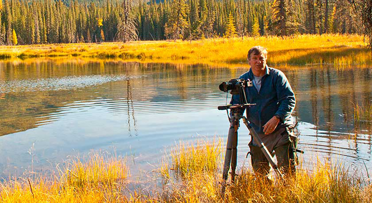 Robert Berdan in a pond with waders taking photos by Halle Flygare